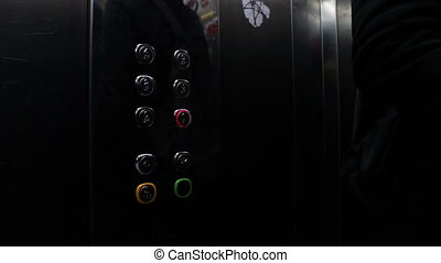 Man presses a button the floor in an elevator - People...