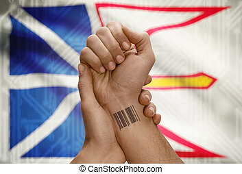 Barcode ID number on wrist of dark skin person and Canadian...