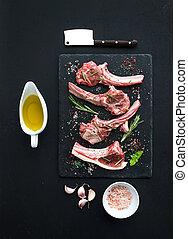 Raw lamb chops. Rack of Lamb with garlic, rosemary and...
