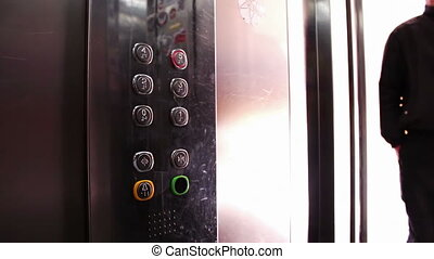 Presses a Button In An Elevator - People inside the...