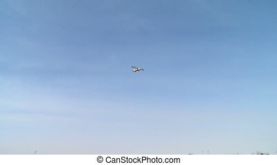 Single-engine plane flies over airfield and windsock