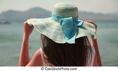 Woman in hat looking at sea
