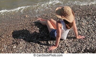woman in a hat sitting on the seashore