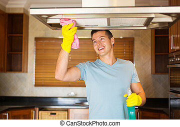 young man cleaning kitchen - happy young man cleaning...