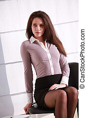 Sexy secretary in blouse and mini skirt sitting in a office