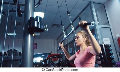 An attractive girl on the simulator training in the gym
