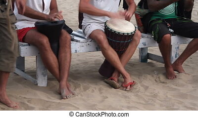 man playing on drum at the beach at summer day