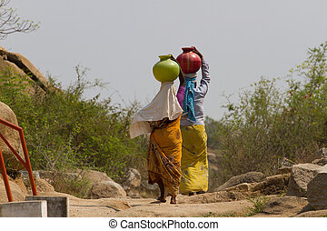 Two Indian women carry water on their heads in pots - Two...