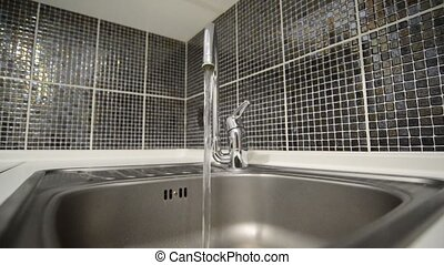 Water pours from the faucet in kitchen - Water pours from...