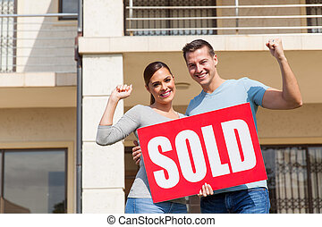 young couple holding sold sign in front of their old house