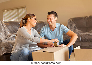 couple packing for new house - cheerful couple packing for...