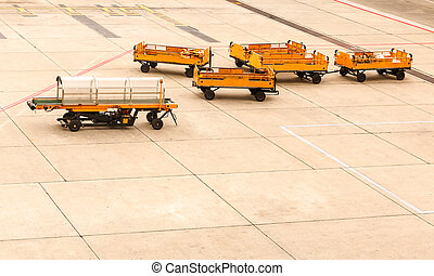 Empty transporting baggage trailer to airplane on runway.