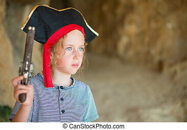 Little girl in pirate costume with musket gun near the cave...