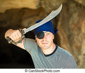Male pirate with sword near the cave entrance