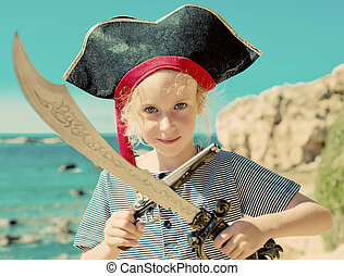 Little girl in pirate costume with sword and old musket gun