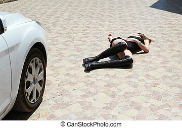 Car accident with woman lying unmoving on the ground