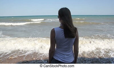 silhouette of lone woman on the background of the sea and waves
