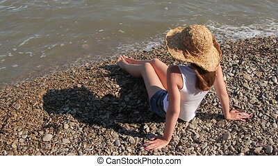 woman in a hat sitting on the beach