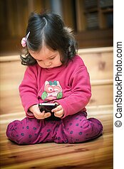 Little girl holding cell phone - Little cute curious baby...