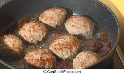 pan roasted great big, tasty burgers - frying the meatballs...