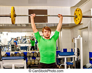 Man in working with dumbbells his body at gym - Man in green...