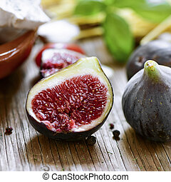 figs on a rustic wooden table - closeup of some appetizing...