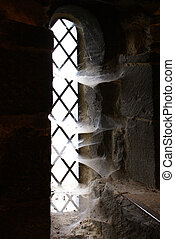 Lancet window with spider webs in ancient tower