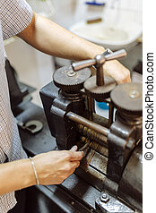Goldsmith crafting metal with the help of a press