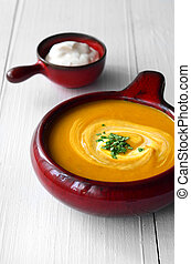 Butternut squash soup with cream on white wooden table