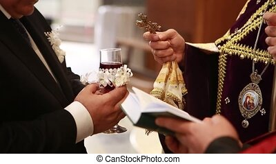 Cross priest consecrates glass of wine