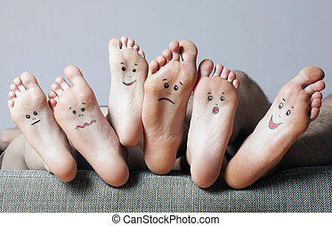 Human soles with painted faces. - Human soles with painted...