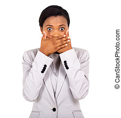 surprised african american woman covering her mouth with...