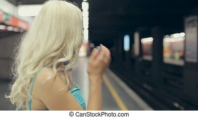 Blonde waiting train at the metro station in Milan