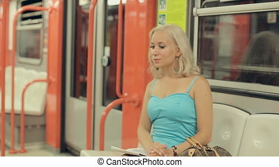 Attractive blonde sitting in a subway car in Milan -...