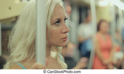 Thoughtful blonde wearing a blue dress standing in a subway...