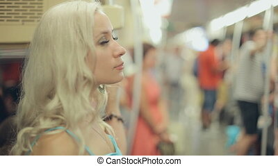 Cute blonde in a crowded metro car - Cute blonde in the...