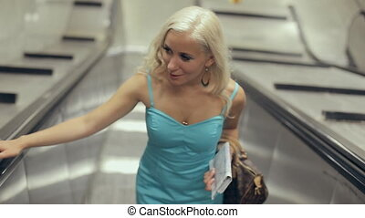 Beautiful blonde raise up on moving staircase in the metro -...