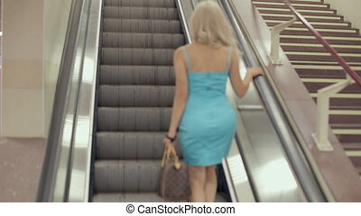 Young woman on a moving escalator - Young woman on moving...