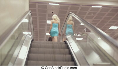 Young woman comes down from moving escalator