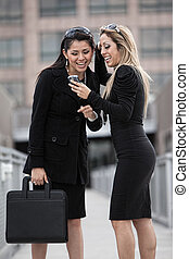 Two attractive hispanic businesswomen walking outdoor