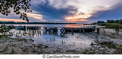 Panormic landscape with boats on the water near the old pier. Beautiful view of colorful sunset on the lake