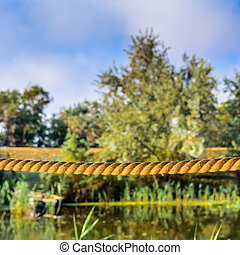 Tightrope on a background of trees and water. Horizontal scene of rope, blue sky and calm lake in the summer