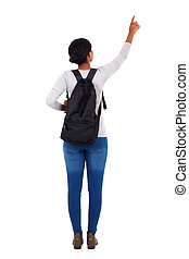 back view of african college girl pointing empty space on...