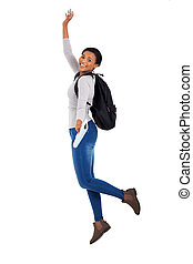 young female african college student jumping - cheerful...