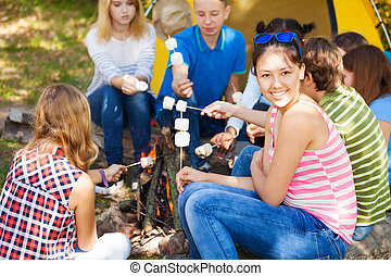 Friends sit on campsite with smores sticks - Friends sitting...