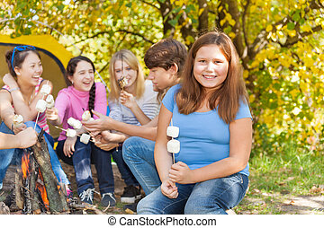 Teenagers sit on campsite with marshmallow sticks -...