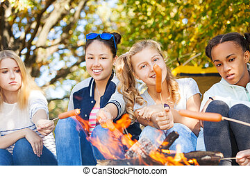 Teen friends sit on campsite with sausages on sticks near...