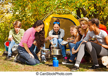 Teenagers cook soup in metallic pot near tent - Teenagers...