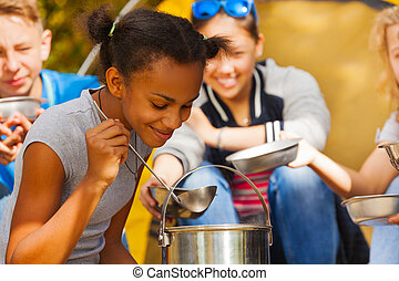 Close-up of African girl cooking soup at campsite - Close-up...