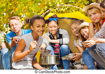 African girl cooks soup in pot at campsite sitting near...